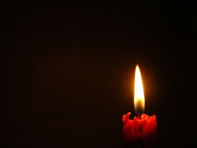 Burning_candle_on_black_background